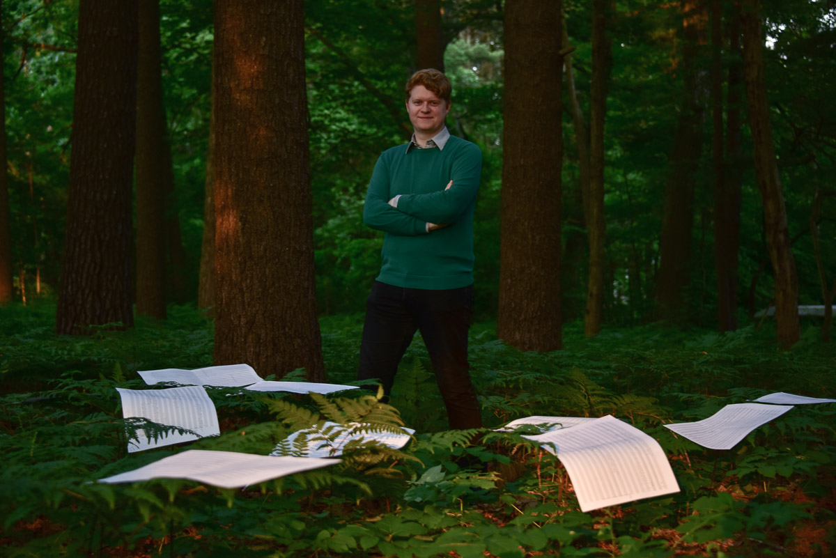 Composer Michael Small in forest surrounded by music sheets