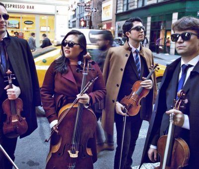 String quartet musicians standing on a busy city street