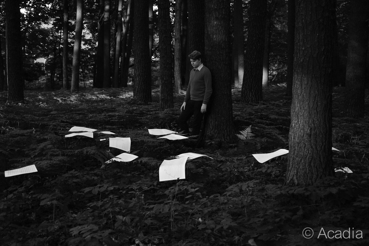 Michael Small in forest with music sheets on the ground by his feet