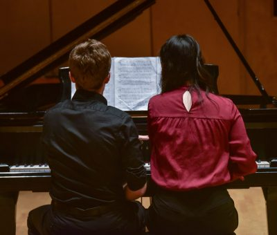 Two piano students side-by-side on a piano bench
